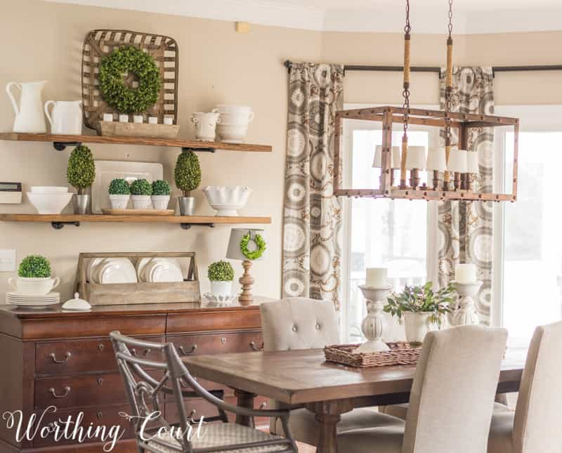 farmhouse style open shelves filled with white decor accents, dining table with white centerpiece, tobacco basket, faux greenery, industrial light fixture