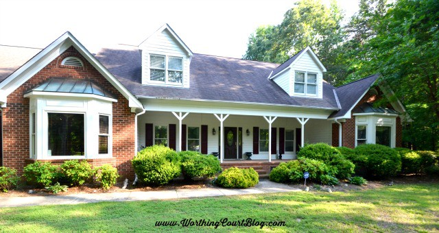 red brick two story ranch style house with large front porch