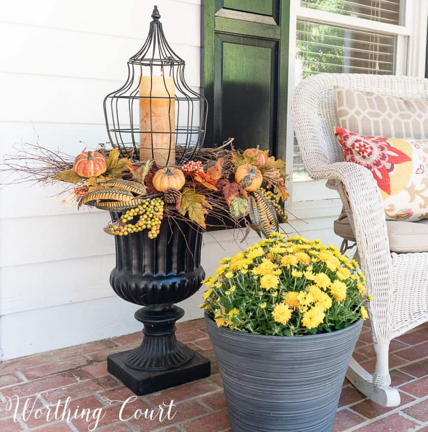 black urn with fall picks and a lantern in the middle