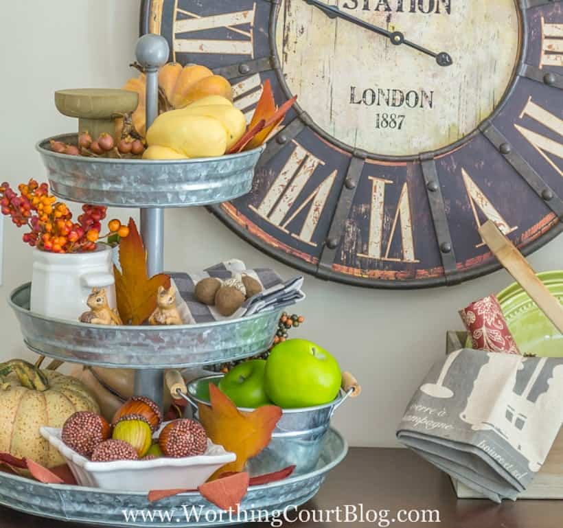 metal tiered tray filled with a variety of fall decorations