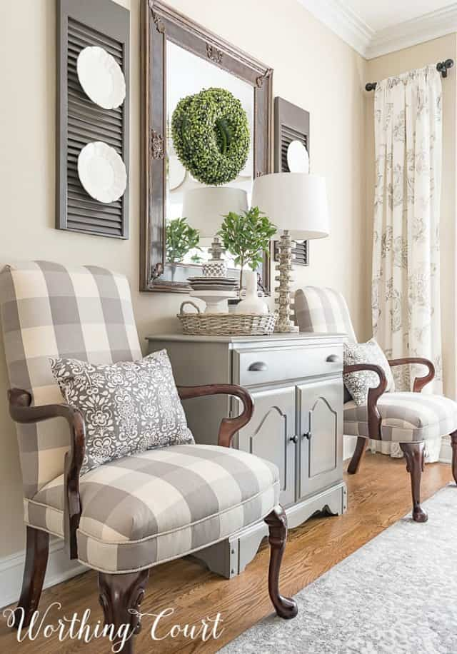 Martha Washington side chairs upholstered with gray and white buffalo check fabric with a small gray chest between them