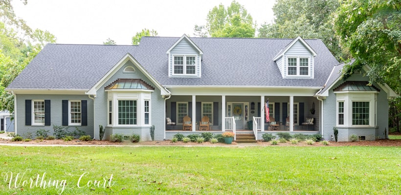 two story brick house painted gray with two bay windows and front porch