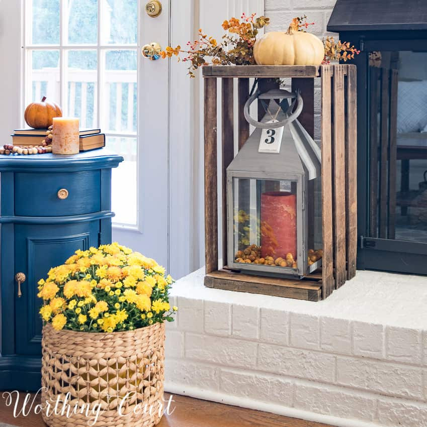 wooden crate on fireplace hearth with pumpkin on top