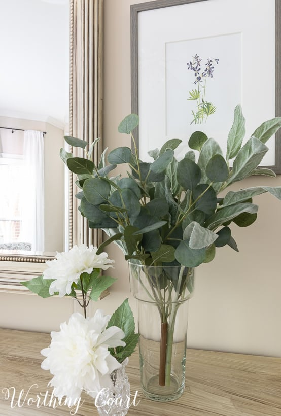 vase with faux eucalyptus stems and faux white dahlias displayed on a bedroom dresser
