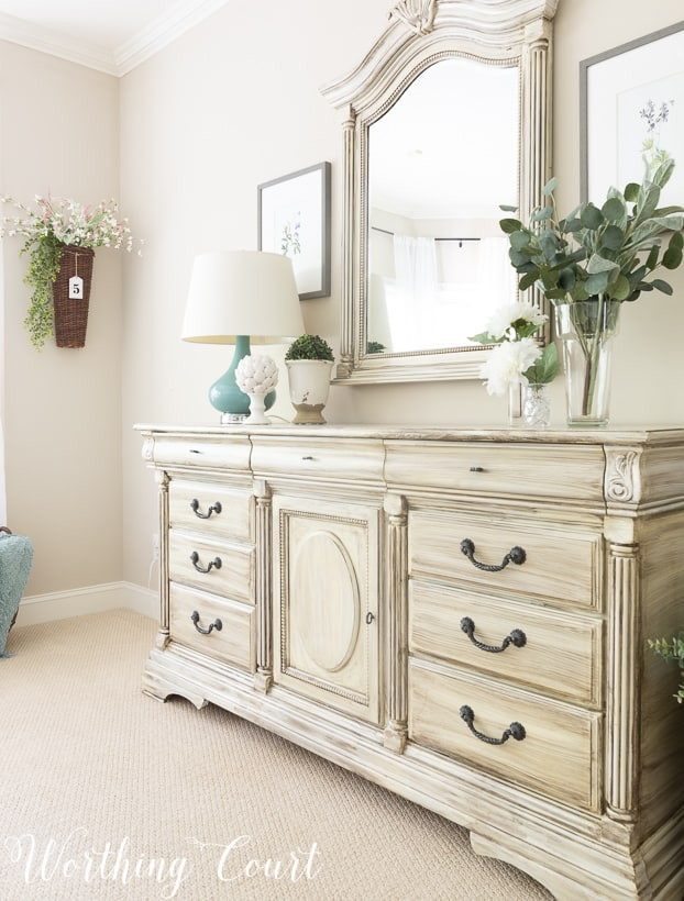 Traditional bedroom dresser painted with white paint and dry brushed with gray paint.