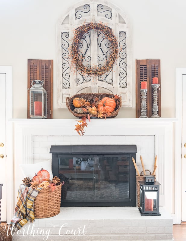 Fireplace decorated for fall with baskets and pumpkins