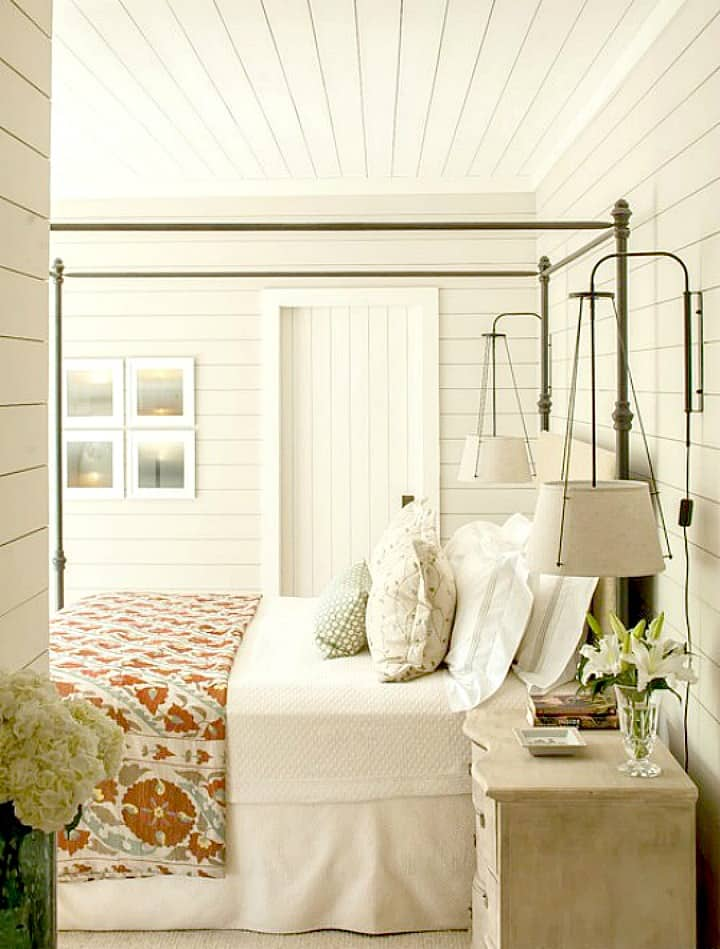 How to decorate a fixer upper farmhouse bedroom with white shiplap walls with metal bed and quilt and end table lights