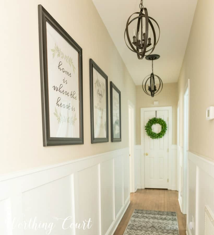 neutral hallways with board and batten walls and pendant lighting