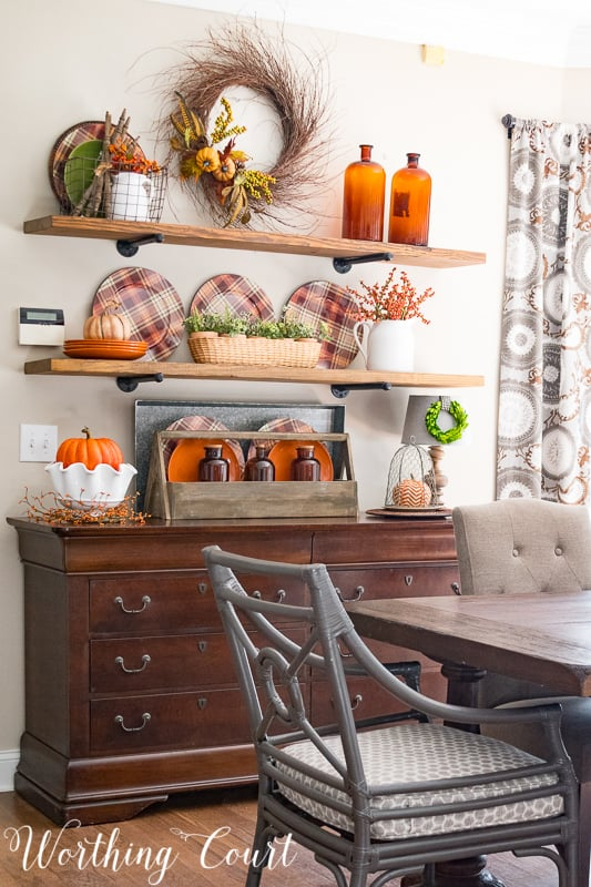 Kitchen shelves decorated with plaid plates, amber glass and a fall wreath.