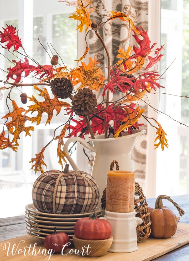 fall centerpiece with plaid pumpkins and fall foliage