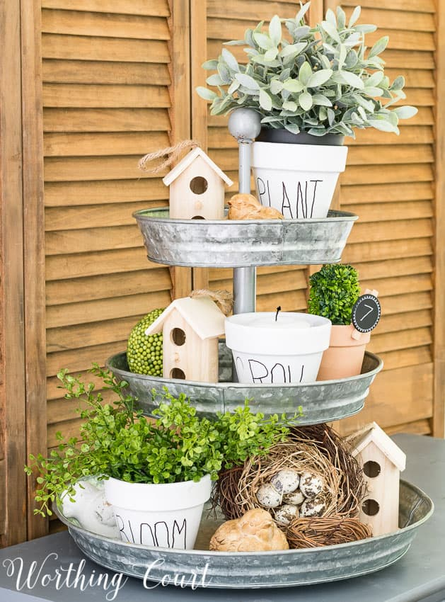 tiered tray decorated for spring with birdhouses flower pots and greenery