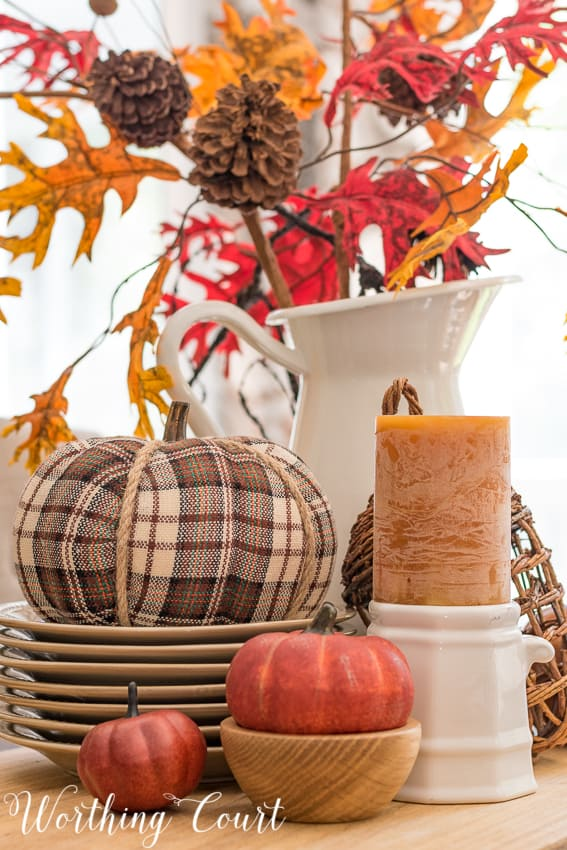 Fall centerpiece with a plaid pumpkin, small faux pumpkins and fall colored candle.
