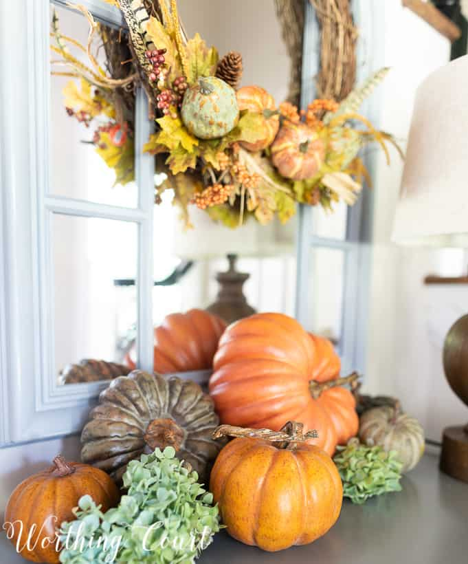 Artificial pumpkins arranged on a gray chest in the foyer