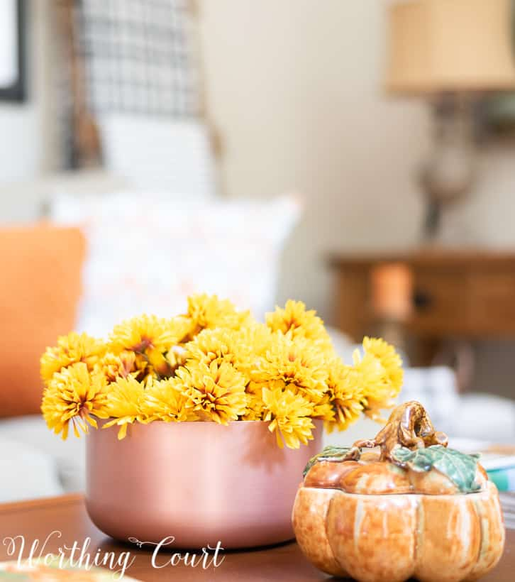Copper bowl filled with bronze mums and pumpkin container on a coffee table