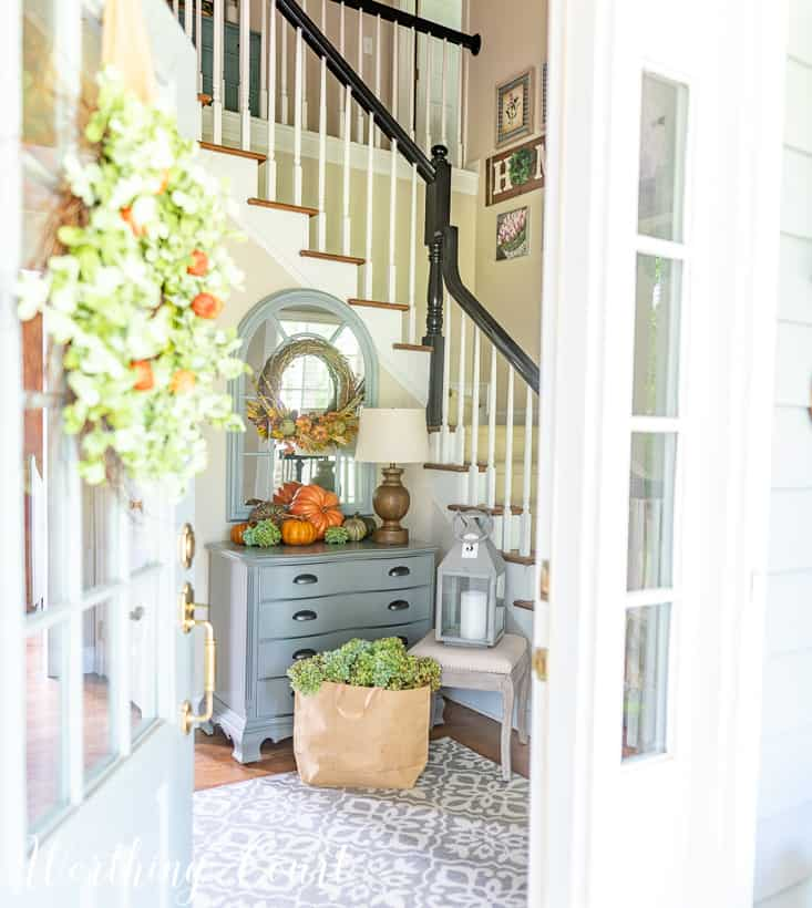 Fall foyer decorations with pumpkins on a gray chest