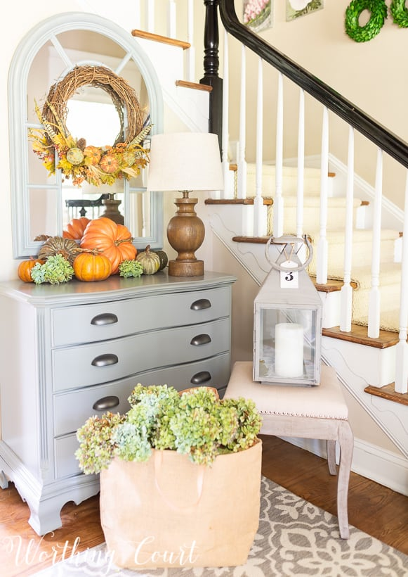 gray chest with fall pumpkins and fall wreath