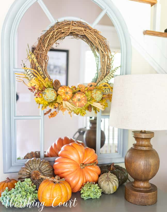 Variety of pumpkin colors displayed together on a small chest, with a fall wreath hanging on a mirror above the chest.