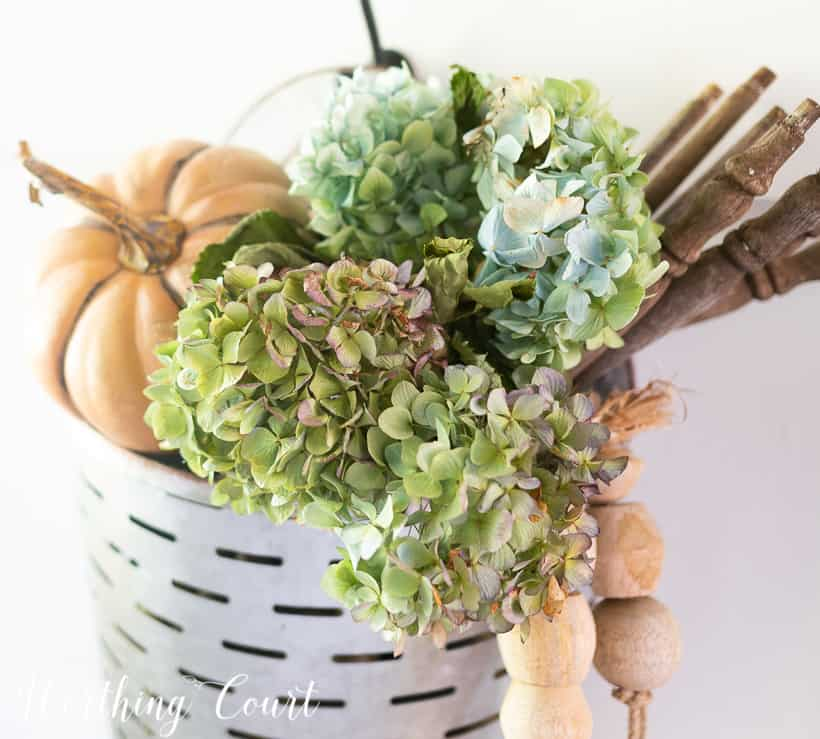 hanging bucket filled with dried hydrangeas, wood beads and a pumpkin