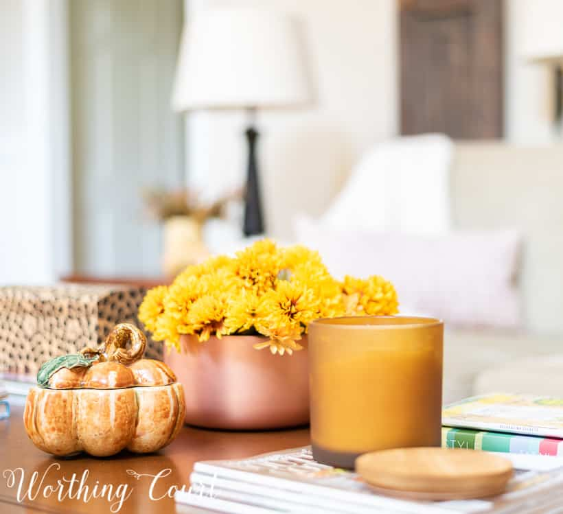 coffee table decorated for fall with mums in a copper container and a pumpkin