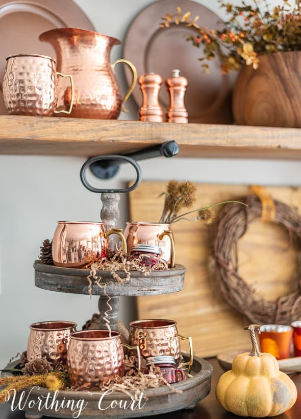 shelves decorated for fall with copper accessories