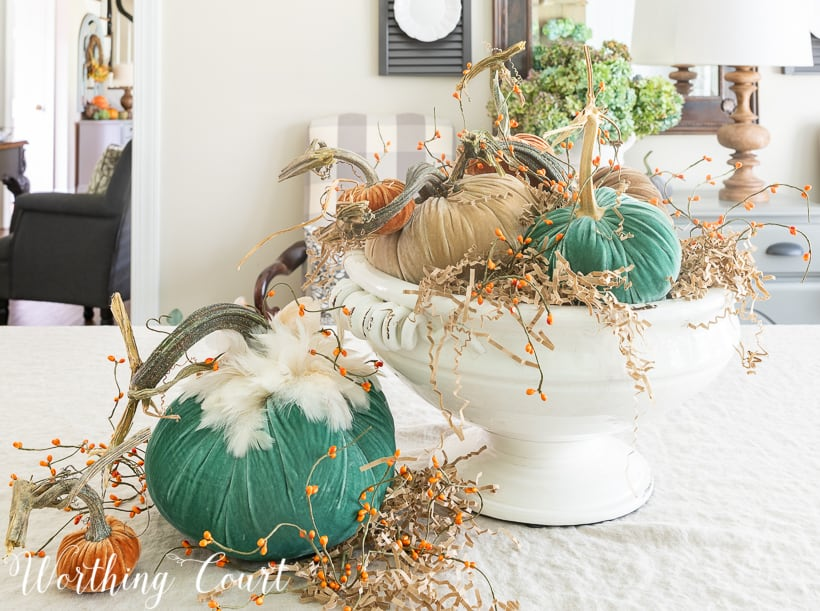 The velvet pumpkins are in a white ceramic bowl, with a large green and a small orange pumpkin beside it on the table.