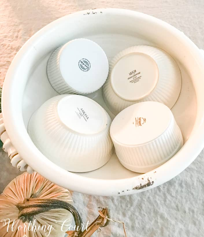 Placing the bowls upside down in the white urn.