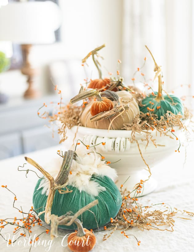 Fall centerpiece with velvet pumpkins green, neutral and orange.