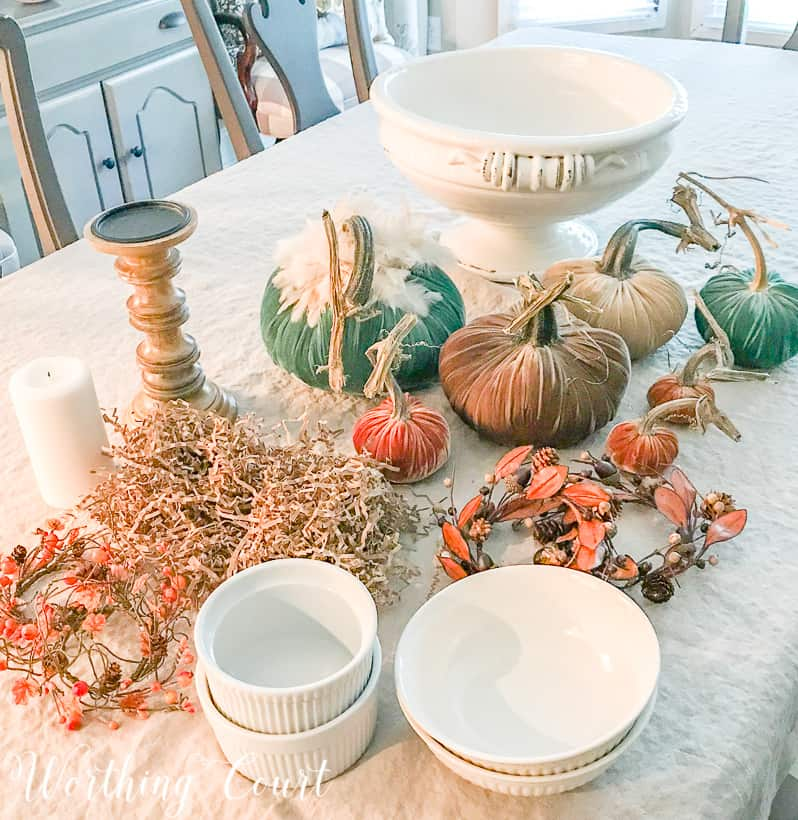 The velvet pumpkins, bowls, candlestick, with a candle and the white urn on the table.