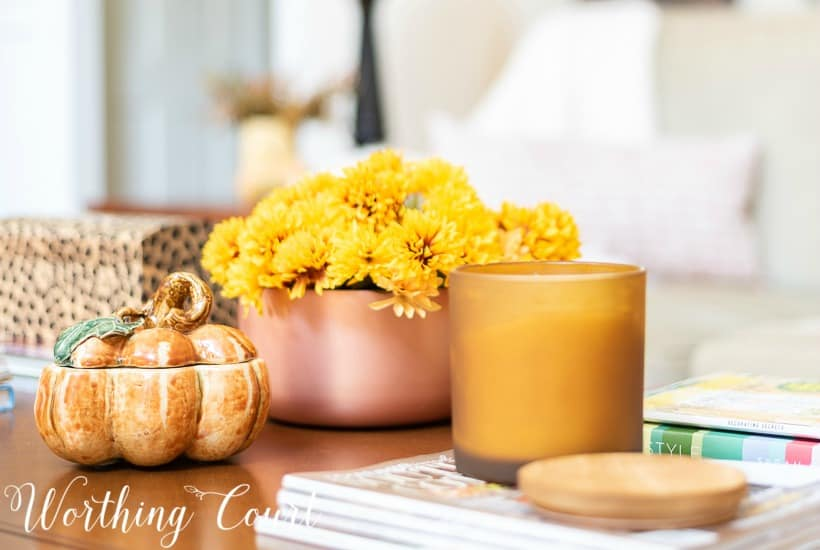 coffee table with pumpkin, mums in a copper container for fall