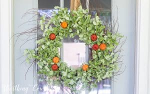 fall wreath with green leaves and faux pumpkins