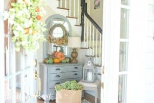 Entryway decorated for fall with pumpkins and a fall wreath