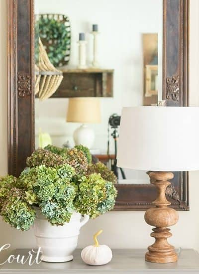 Dried hydrangea arrangement in white vase on gray chest