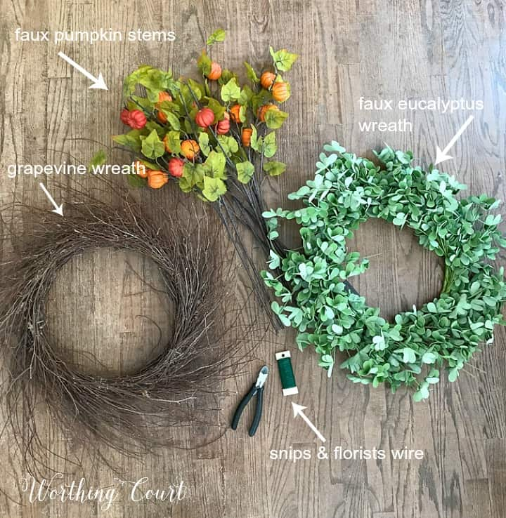 fall wreath with faux pumpkins and green leaves