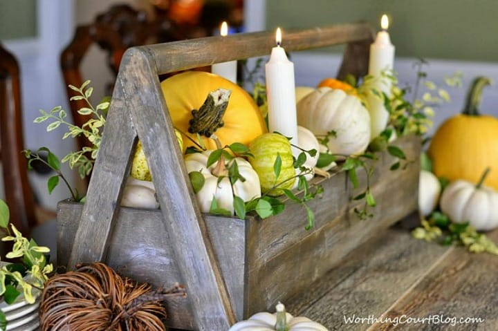 wooden toolbox filled with white and yellow pumpkins, real greenery sprigs and white candles