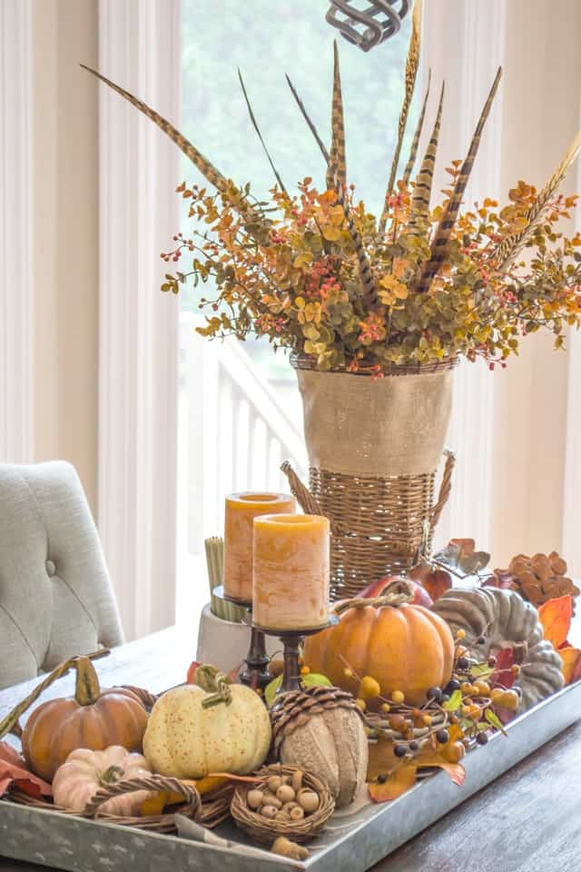 fall centerpiece in a metal tray with fall foliage, candles, pumpkins and feathers