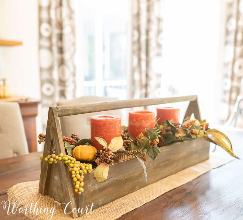fall centerpiece with fall colored candles and fall picks in a long wooden box