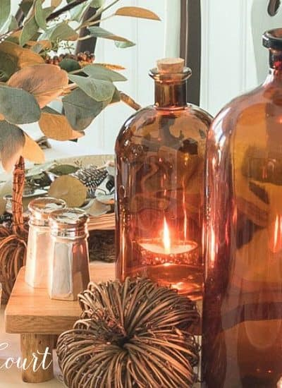 fall centerpiece with neutral colors and amber bottles