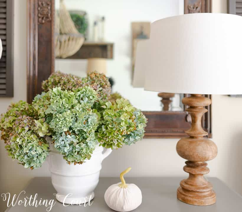 blue hydrangeas in a white vase along with a small white pumpkin