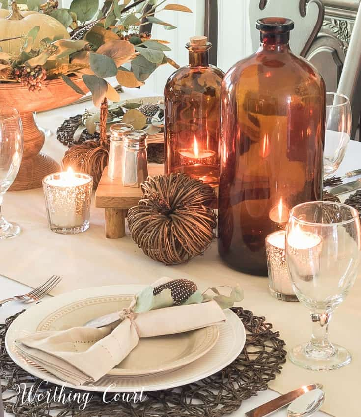 Neutral Thanksgiving tablescape with amber glass bottles