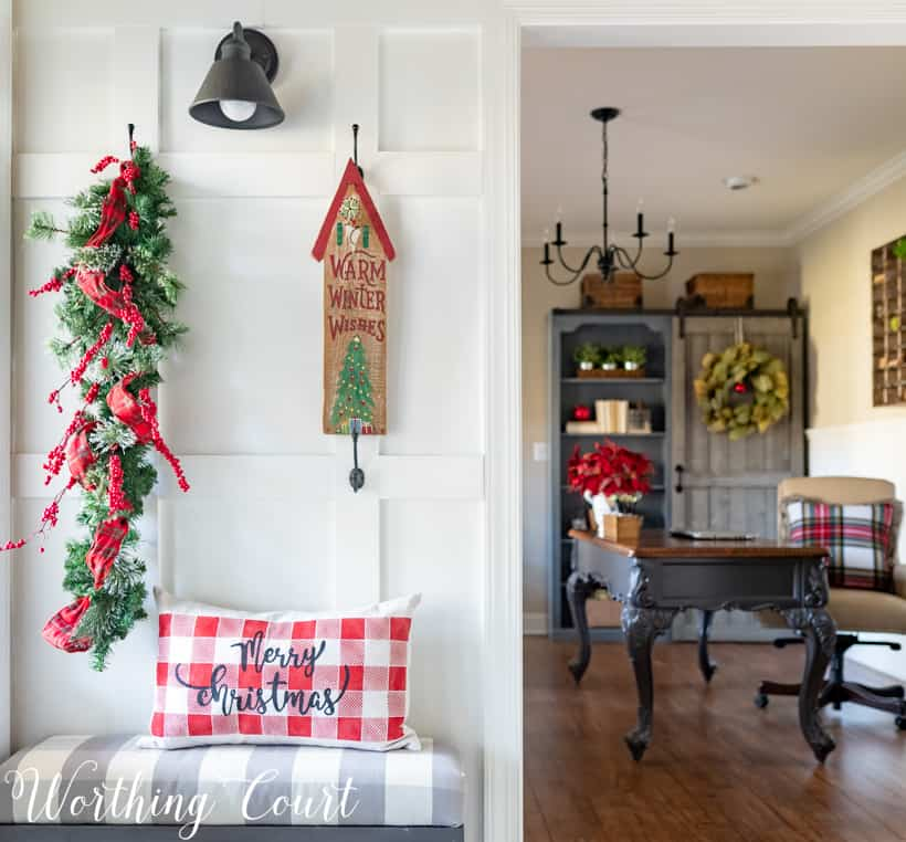 Christmas foyer decor with a plaid pillow on the bench that says Merry Christmas.