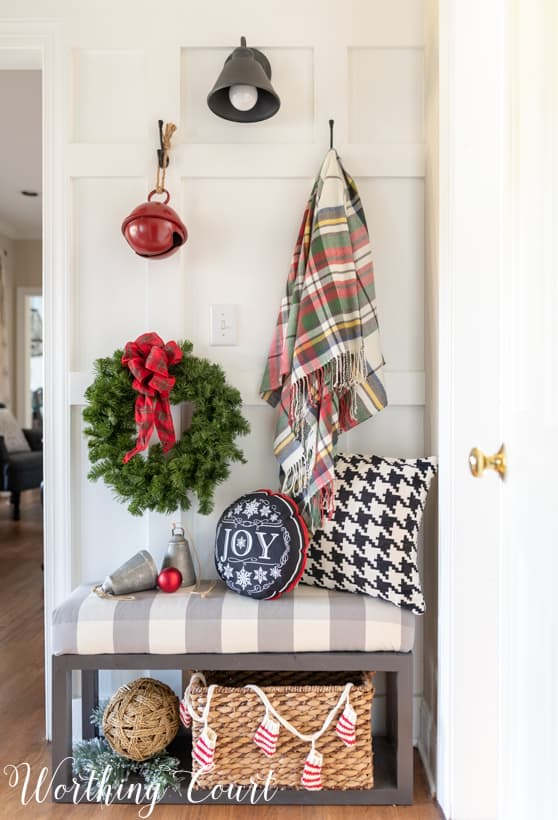 A throw blanket is hanging beside a wreath on the wall.