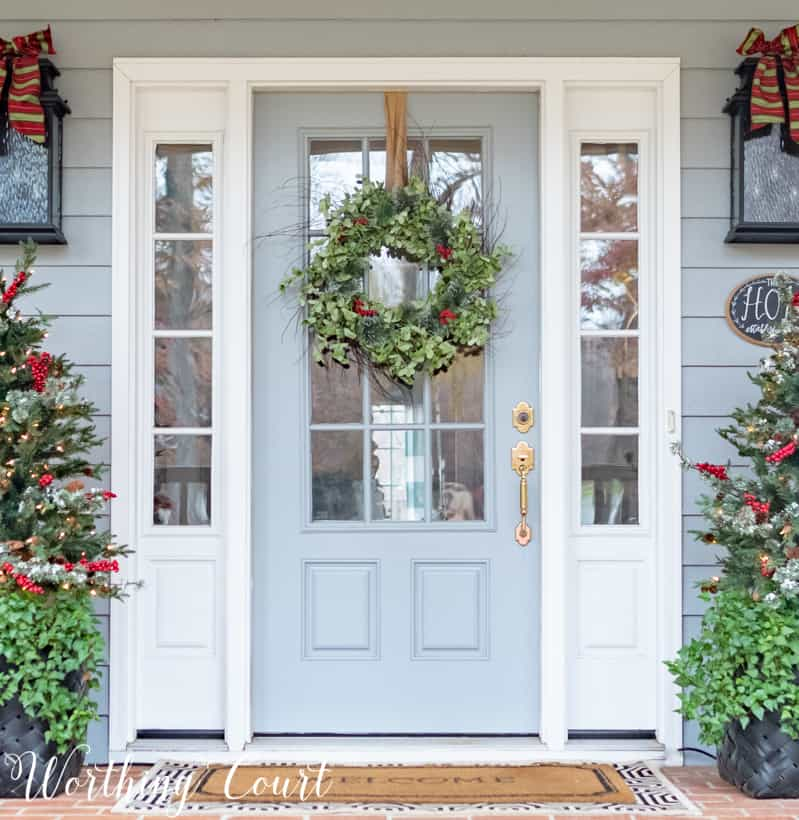 A light blue door with a green wreath and berries on it.