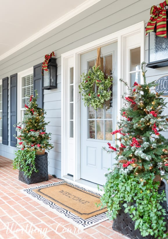 Christmas front porch decor with little Christmas trees flanking the front door.