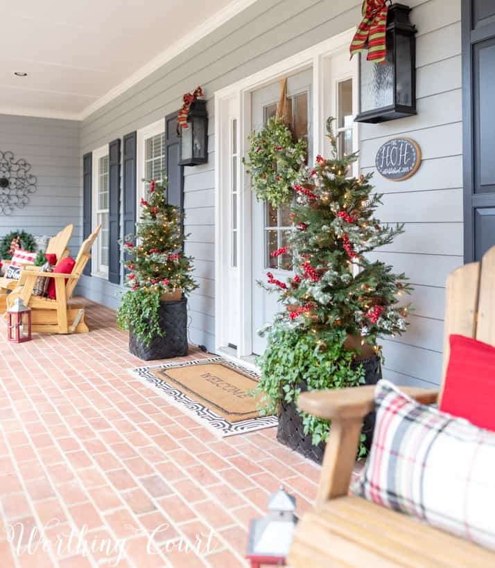 Christmas front porch with Adirondack chairs that have plaid and red pillows on them.
