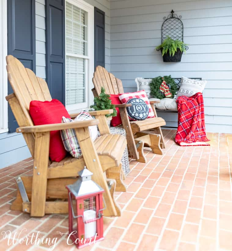 Adirondack chairs with red and plaid cushions and throw blankets are on the chairs.