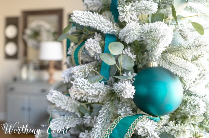 Flocked Christmas tree with teal decor.