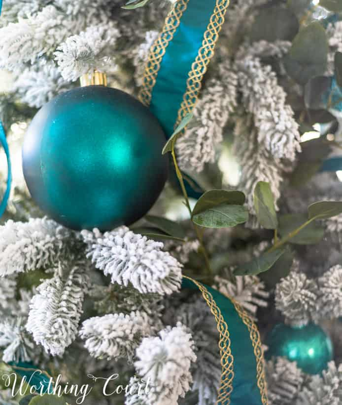 teal ornaments on a flocked Christmas tree