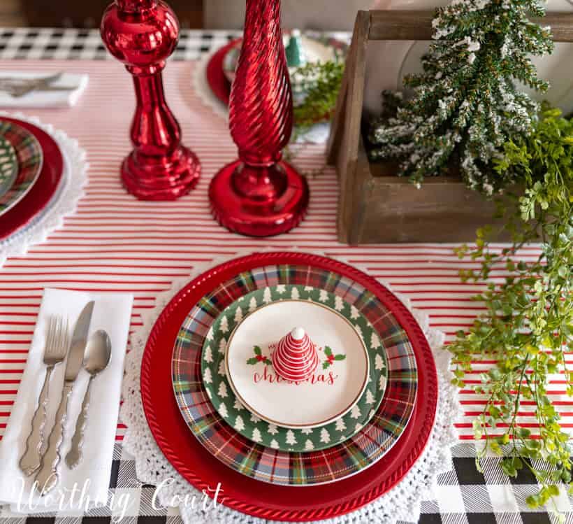 Plaid, red and Christmas plates are on the table.