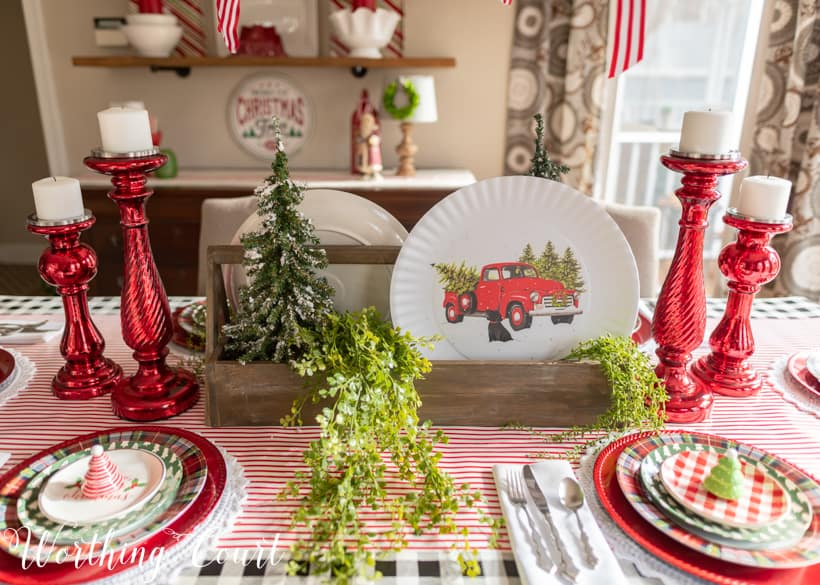 Christmas table centerpiece with a wooden toolbox filled with mini trees and plates with red trucks.