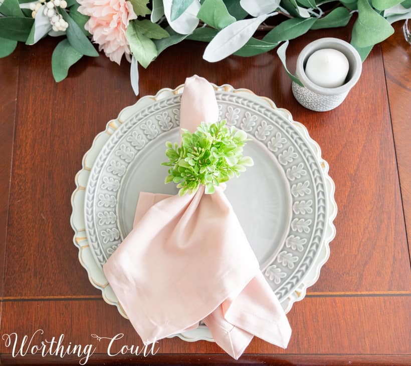 table setting with gray dinner plate and pink napkin